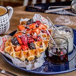 Waffles with cottage cheese, date syrup and fruits.