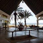 La entrada del hotel es un gran techo con mesas, flores y sofas con cojines, cerca del restauran