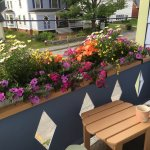 Beautiful flowers on the porch and a view of Main Street with morning coffee. Pristine clean roo
