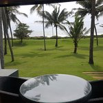 View from the room of the open sit-out balcony, green lawns and coconut trees and sea beyond