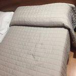una de las camas de la supuesta cama doble... la ropa de cama sin encanto, aburrida y vieja.
