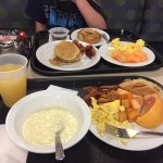 Our breakfast plates: grits, eggs, potatoes, bacon, pastry, cantaloupe, grapefruit, pancakes, sy
