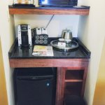 Microwave, fridge and coffee maker in room.