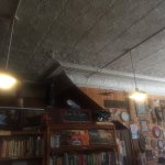 the old tin ceiling, book shelves and more art for sale on the wall.