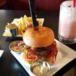 Customized burger with shoestring fries and a red velvet milkshake and tea.