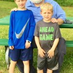 Grandsons rest in the playground park with Grandpa.