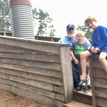 Grandpa and grandsons visit the wooden ship in the wooden canal.