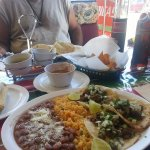 Foreground is the taco platter with beans and rice. Tamale on th side.