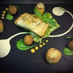 Pan Seared fillet of cod with crispy crab cake, braised spring leek,potato fondant and lemon cr