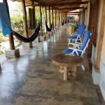 A view outside a room reveals comfy hammocks. The pool is about 20 feet to the left of the porch