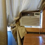 Tucking curtain around window A/C for privacy.