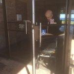 2 elderly people in walkers trying to open 2 doors pushing their walker through wheelchair sign