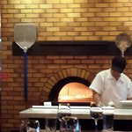 Artisanal pizza being made in a wood-fired oven