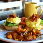 BLGT Eggs Benedict with spinach, bacon, guacamole on a cheese biscuit.