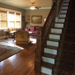 View of the living room and staircase. Vintage furnishings, artwork