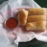 Delicious breadsticks with marinara sauce.