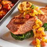 Pan seared salmon filet with wilted baby spinach and orange relish
