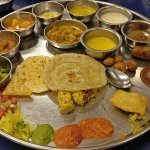 as thali is getting filled with verities of gujrati cuisines