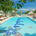 Lush foliage and two-person lounge beds adorn the Main Pool.