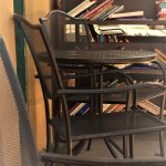 Outdoor seating and two carts of $1 books can be found out front.