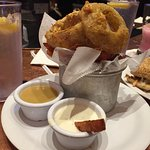 Onion rings and sweet potato fries with dipping sauces