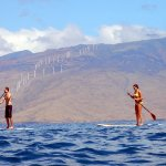 Paddleboarders at Kamaole III beach with Maalaea wind turbines in the background