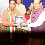 HE LG Prof Shri Jagdish Mukhi felicitating Shri TSG Bhasker. Applauded by HE MP Shri V P Ray