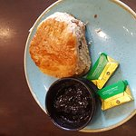 A flat white coffee and a scone and jam