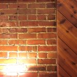 Lovely warm glow of red brick and pine in our room