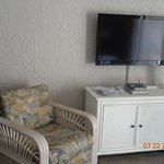 A view of the flat screen tv, chairs in living room- 1 bedroom unit