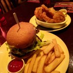 Beef burger, fries and side dish of battered onion rings