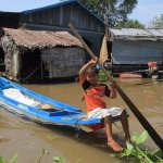 Girl rowing a boat around the floating village