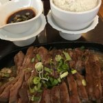 sliced steak with separate spicy sauce and coconut rice