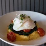 Polenta breakfast, poached eggs, spinach and tomato