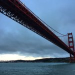 Under the Golden Gate Bridge with view of the city. Sunset Cruise.