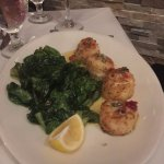 Scallops with fried spinach.