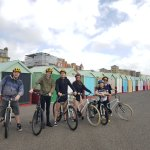 A family bike tour stops of at the beach huts in Hove