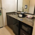 Counter area with sink, coffee maker, mini fridge and microwave.