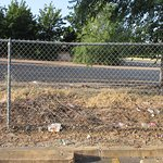 Litter and chain link fence in parking lot