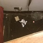 Trash behind bedside table, open electric socket