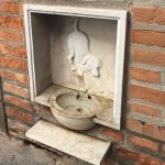 Dog watering bowl on street built into hotel wall