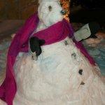 Muñeco de nieve en la puerta de la cabaña