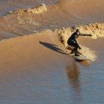 A surfer rides the Tidal Bore on the Petitcodiac River at Moncton