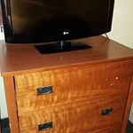 "Dresser with missing handle and 32"" flatscreen TV."