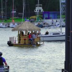 Weekend revellers cruise in style aboard a tropical hut-themed boat along the Canalside district