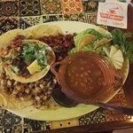 Plato de tacos variados con salsa de frijoles y guacamole