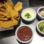 Chips with salsa, cheese dip, bean dip, and guacamole.