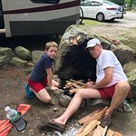 Grandpa making a fire with grandson in beautiful rock fire pit at our campsite.