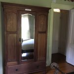 Large cabinet for hanging clothes, corner of iron bed - looking from bedroom into hallway of sui