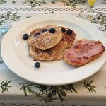 Pancakes and blueberries with a side of fresh, tender and good tasting Pemel (spelling?) ham.